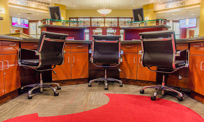 Image of chairs at reception style desk for higher ed casework page